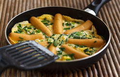 Omelette with sausages and herbs in frying pan on rattan table Royalty Free Stock Photos