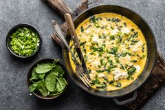 Omelette with spinach and cheese in a pan top view. Omelette with spinach and cheese in a pan on the concrete background top view stock photos