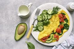 Omelette stuffed with spinach, cheese, avocado and salted salmon.Top view with copy space. Omelette stuffed with spinach, cheese, avocado and salted salmon on a royalty free stock photos
