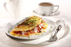 Omelette. Tasty omelette with ham and tomatoes stock images