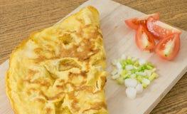 Omelette thaïlandaise avec les tomates et l'oignon blanc sur la planche à découper photos stock