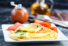 Omelette. With tomato on the white board royalty free stock photos