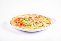 Omelette on a plate. Omelette with tomatoes and fresh corn salad on a white background stock images