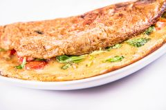 Omelette on a plate. Omelette with tomatoes and fresh corn salad on a white background stock photo