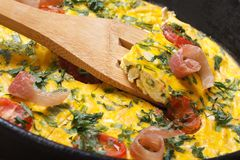 Omelette with tomatoes, ham and herbs macro horizontal Royalty Free Stock Photo