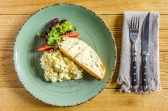 Omelette, tomatoes, herbs and bread on a green plate, cutlery, on a wooden table. View from above Royalty Free Stock Photos