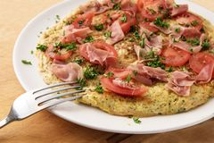 Omelette with tomatoes, prosciutto ham and parsley garnish and a. Fork on a white plate on a rustic wooden table, close up, selected focus, narrow depth of Stock Images