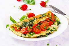 Omelette with tomatoes, spinach and green onion on white plate. Stock Photo