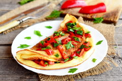Omelette with vegetables on a plate, fork and knife on old wooden background. Colorful omelette stuffed with roasted red pepper Royalty Free Stock Photography