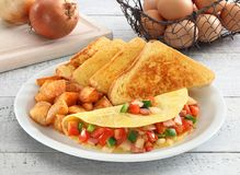 Omelette breakfast. Omelette wiith toasted bread and potatoes Royalty Free Stock Images