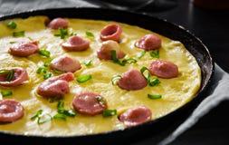 Omelette z kiełbasą w smaży niecce na drewnianym stole Obraz Royalty Free