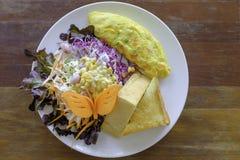 Omelette z mieszanki sałatką i gęstym chlebem w bielu talerzu Zdjęcie Royalty Free