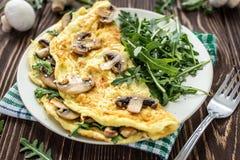 Omelette z pieczarkami i arugula na drewnianym tle fotografia stock