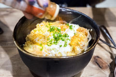 Omelettspitzenschweinefleisch knusperig und Reis im Schüsselschwarzen stockfotos