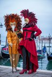 Omen with colorful Venetian costume and mask. VENICE, ITALY - FEBRUARY 7, 2018: Women with colorful Venetian costume and mask in front of gondolas in Piazza San stock images