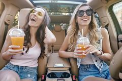 Omen holding cocktails in plastic cups. Smiling women holding cocktails in plastiups sitting in the car royalty free stock images
