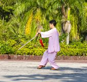 Omen in the street in the Park gymnastics WUSHU. Sanya, China : 11 NOV 2017: Women in the street in the Park gymnastics WUSHU royalty free stock photos