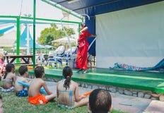Omer, ИЗРАИЛЬ - гимнаст девушки в красном кимоно скача с белой лентой на зеленом этапе перед детьми, 25-ое июля 2015 Стоковые Изображения