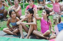 Omer - пиво-Sheva, ИЗРАИЛЬ - девушки в купальных костюмах сидя на траве, 25-ое июля 2015 Стоковое Изображение