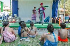 Omer (пиво-Sheva), ИЗРАИЛЬ - 2 клоуна на этапе около бассейна перед детьми, увиденными от позади, 25-ое июля 2015 Стоковое Изображение