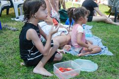 Omer (Beer-Sheva), ISRAEL -The boy eating slices of watermelon on the grass with other people close, July 25, 2015 Royalty Free Stock Photo