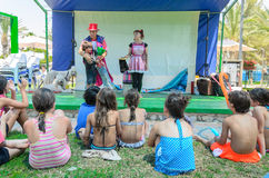 Omer (Beer-Sheva), ISRAEL Children sitting on the grass with his back near the summer stage and two clowns , July 25, 2015 Royalty Free Stock Photo