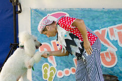 Omer (Beer-Sheva), ISRAEL - ,Clown in a cap shakes paw white poodle on stage -July 25, 2015 Royalty Free Stock Image