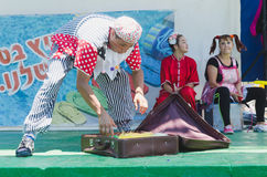 Omer (Beer-Sheva), ISRAEL -The man - clown with an old brown suitcase on green summer stage and two assistants, July 25, 2015. Beer-Sheva, ISRAEL -The man royalty free stock photo