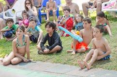 Omer - bière-Sheva, ISRAËL - enfants sur l'herbe observant la vue de poolside d'été, le 25 juillet 2015 Photographie stock libre de droits