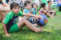 Omer (bière-Sheva), l'ISRAËL garçon avec du ballon de football et d'autres enfants s'asseyant sur l'herbe pendant l'été, le 25 ju Photographie stock libre de droits