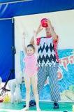 Omer (bier-Sheva), ISRAËL - Clown met een bal en een meisje in een roze badpak, 25 Juli, 2015 Royalty-vrije Stock Afbeeldingen