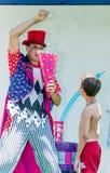 Omer (bier-Sheva), ISRAËL - de Clown werpt tennisballen in wit GLB De jongen kijkt, 25 Juli, 2015 Stock Afbeeldingen
