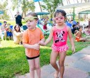 Omer (cerveza-Sheva), ISRAEL - muchacho y muchacha en gafas de la natación con los otros niños en la hierba por la piscina, el 25 Fotos de archivo libres de regalías