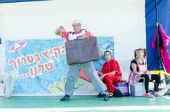 Omer, ISRAEL - el hombre - payaso hace juegos malabares la maleta marrón vieja en la escena con un caniche y un ayudante, el 25 d Foto de archivo libre de regalías