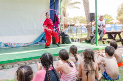 Omer, ISRAEL -The girl in a scarlet kimono with a hoop and a clown performing on the summer stage in front of the pool child Royalty Free Stock Photos