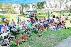 Omer, ISRAEL - niños y padres - los funcionamientos del verano de la audiencia en la piscina en la hierba, el 25 de julio de 2015 Fotografía de archivo
