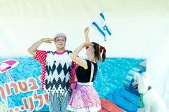 Omer (öl-Sheva), ISRAEL - två clowner med den israeliska flaggan och en vit pudel - Juli 25, 2015 i Israel Royaltyfria Bilder