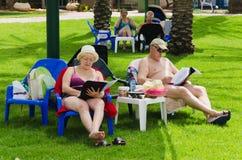 Omer, Negev, ISRAEL - 27 de junho, mulher e homem que sentam-se lendo um livro pela associação em um local verde Omer, Negev, o 2 Imagem de Stock