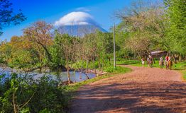 OMETEPE, NICARAGUA, MAY, 14, 2018: Unidentified people riding a horse in a heavy ecosystem with a goregous view of. Volcan Concepcion in the horizont, close to stock photo
