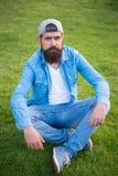 Omfamna den estetiska streetwearen Sexig man som sitter på grönt gräs Skäggig man i tillfällig grov bomullstvillstil caucasian ma royaltyfri fotografi