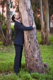 Omfamna en trädstam Arkivfoto