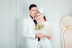 Omfamna härliga nygifta personer i elegant inre arkivbild