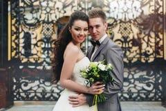 Omfamna nygifta personer framme av portarna Royaltyfri Bild