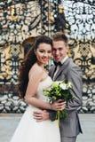 Omfamna nygifta personer framme av portarna Royaltyfri Fotografi