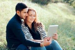 Omfamna par som är förälskade med den Digital minnestavlan på utomhus- datum royaltyfri bild