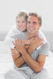 Omfamna par som ler på kameran Royaltyfria Bilder