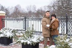 Omfamna par som ser kameran Royaltyfria Bilder