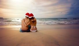 Omfamna par som ser solnedgång med julhatten Arkivfoto