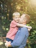 Omfamning av fadern och den lilla sonen royaltyfria foton