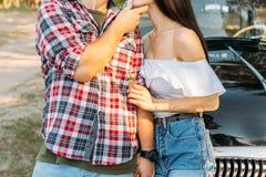 omfamning Förälskelse och affektion mellan ett ungt par på parkera, nära den gamla bilen en grabb i en plädnivå och jeans, en fli royaltyfri foto